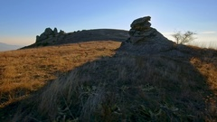 Aerial mountain peak grass rocks skyline autumn sunny day blue sky sun light Stock Footage