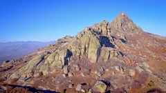 Aerial mountain summit rocks grass autumn skyline sunny day clear blue sky wide Stock Footage