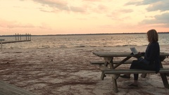 Tracking shot of lady watching TV on her tablet at the beach at sunset Stock Footage
