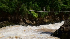 Tourist at the rope bridge above tempestuous wild water,  Don Det,  Laos Stock Footage