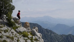 A mountain biker standing on a pile of boulders admiring the view. Stock Footage