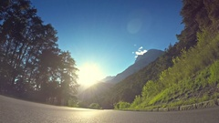 POV vehicle drive car travel nature mountain road green trees sunshine blue sky Stock Footage