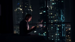 Young man browsing web on tablet computer sitting on bed at home at night Stock Footage