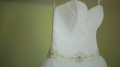 Wedding dress with crystal belt hangs on peg Stock Footage