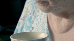 Elderly lady savours cup of coffee Stock Footage