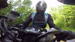 Motorcycle dash mount view of rider tight corner in forest Stock Footage