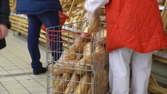 Supermarket employee lays out the bread on the shelf in the bread section Stock Footage