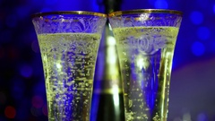 Bubbles sparkling wine in glasses. In the background, bokeh lights and garlands. Stock Footage