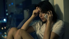 Sad, worried woman talking on cellphone by window at home at night Stock Footage