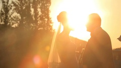 Bride and groom kiss in bright rays of evening sun Stock Footage