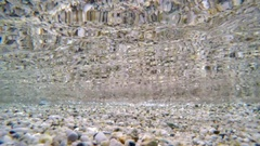 Clear sea shallow water underwater exploring waves pebbles bottom diving Stock Footage