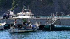 Fishing boats swinging on the water, anchored to a jetty while fisherm Stock Footage