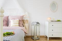 Bed, dresser and decorative lantern Stock Photos