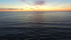 Aerial shot of the sun setting over the ocean horizon. Stock Footage