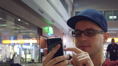 Nerdy man in black rim glasses scrolling app in his mobile phone at the airport Stock Footage