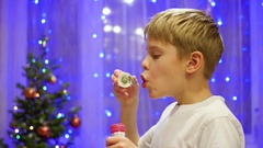 Teen blowing soap bubbles at home. In the background, bokeh lights and garlands. Stock Footage