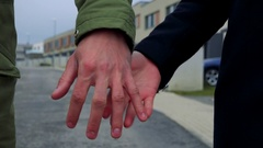 Couple holds hands - detail - street in the background Stock Footage