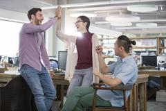 Architects high fiving in the office Stock Photos