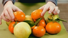 Funny little boy holding mandarins in front of his eyes and having fun Stock Footage
