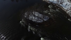 Aerial spin above rapids and stone arch bridge in winter 4k Stock Footage