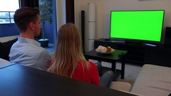 A young, attractive couple watches a TV with a green screen in a cozy living Stock Footage