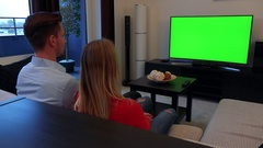 A man and a woman watch a TV with a green screen in a cozy living room, then Stock Footage