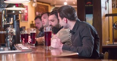 Friends talks drinks beer at pub bar 4k close-up video. Men drinks lager ale Stock Footage
