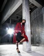 Young beauty african american woman in red coat  strange build Stock Photos