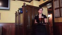 Walking waiter brings beer glasses men HD video pub bar. Camera before girl Stock Footage