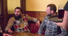 Waiter brings beer glasses men 4k video pub bar or restaurant.  Toast cheers fun Stock Footage