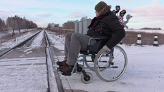 Disabled man on wheelchair try to cross railway crossing Stock Footage