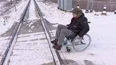 Disabled man on wheelchair near railway crossing Stock Footage