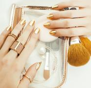 Woman hands with golden manicure and many rings holding brushes, makeup artist Stock Photos