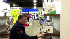 Motion of people looking new security camera inside Best buy store Stock Footage