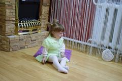 One year old baby girl sitting on the floor. A child playing with wicker ba.. Kuvituskuvat