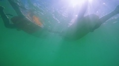 Underwater View Of Two Surfers Lying On Surfboards Resting Stock Footage
