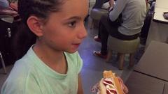 Kid eating hotdog on food court Stock Footage
