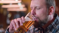 Bearded man drinking beer and enjoying beverage at pub bar HD slow-motion video Stock Footage