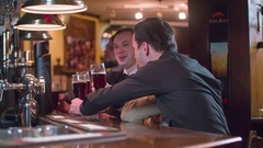 Men friends toast cheers beer drinks at pub bar counter HD slow-motion video Stock Footage