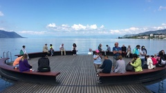 MONTREUX, SWITZERLAND People resting on a pier overlooking Stock Footage
