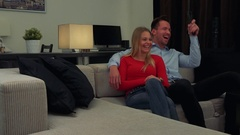 A young, attractive couple sits on a couch in a cozy living room and laughs at Stock Footage