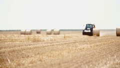 Tractor releases a hay bale, straw. Agriculture background Stock Footage