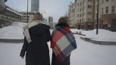 Two friends walking down the street and drink coffee in winter Stock Footage