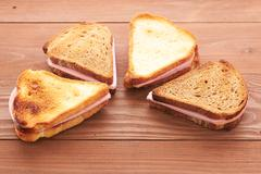 Triangular sandwiches on wooden table Stock Photos