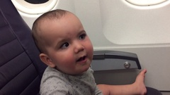 Baby on airplane seat during a flight Stock Footage