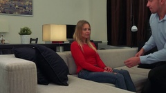 A young, beautiful woman sits on a couch, a man kneels in front of her and Stock Footage