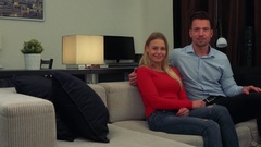 A young, attractive couple sits on a couch in a cozy living room and talks to Stock Footage
