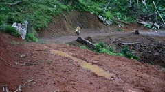 Amateur motocross rider driving the motorcycle  on the muddy road in Laos Stock Footage