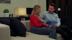 A young, attractive couple on a couch in a cozy living room discuss a DVD they Stock Footage