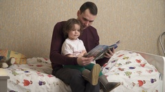 Father is reading the book with his daughter Stock Footage
